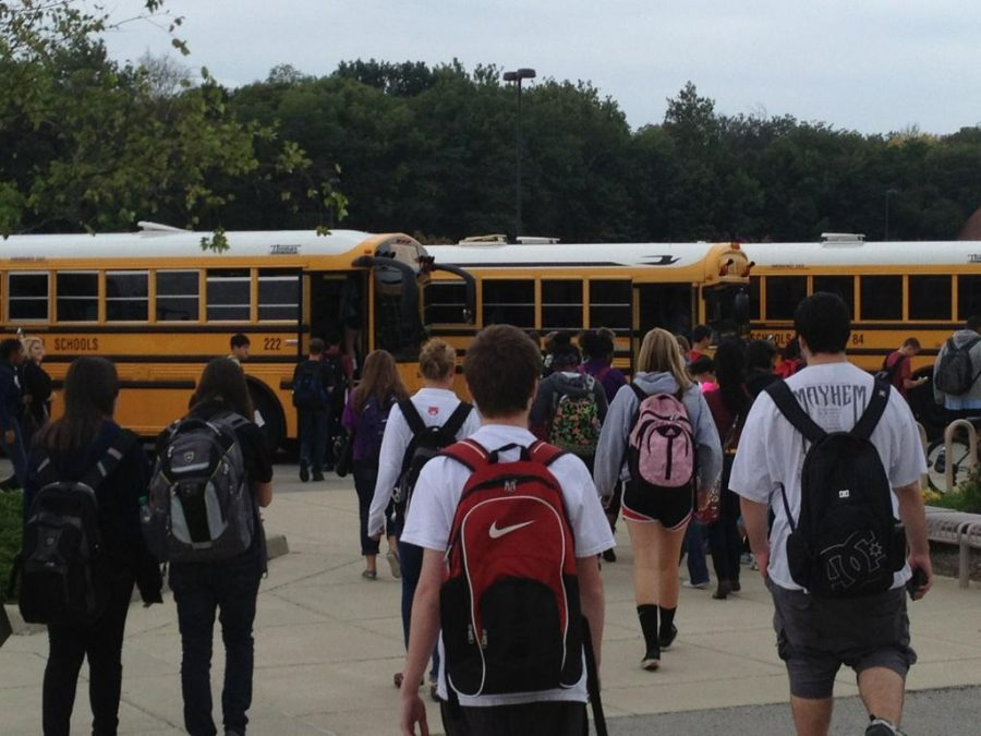 Students walking to get onto buses after school