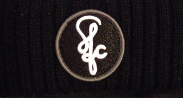 The logo used for Skate for Change. It is embroidered here into a hat, one of the many merchandise, that if purchased the profits go to the charity.