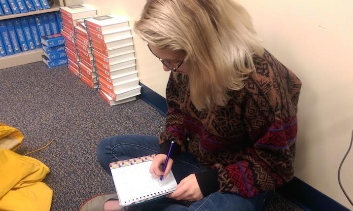 Poetry Club member senior Heather Hollis drafts her next upcoming poem on Dec. 8.