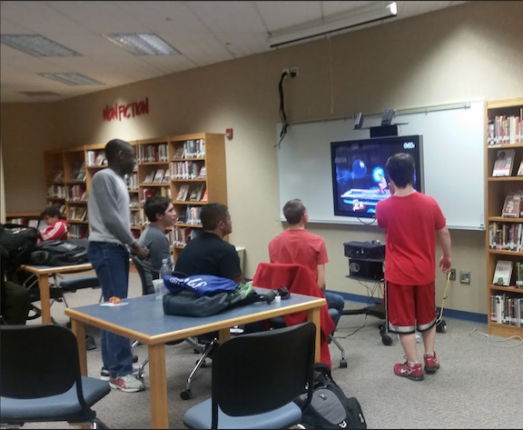 Members gather around the Wii U to play Super Smash Brothers. Photo by Mo Wood.