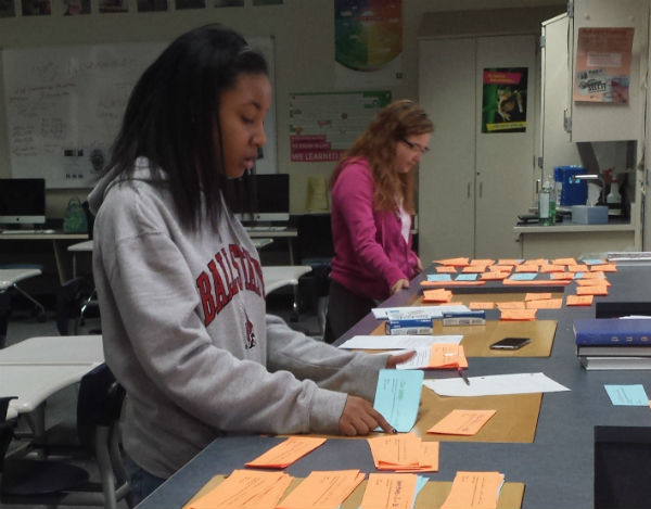 Juniors Tamera Sims and Audree Logan prepare reminder slips on May 5 for students who ordered yearbooks. Photo by Victoria Bernard.