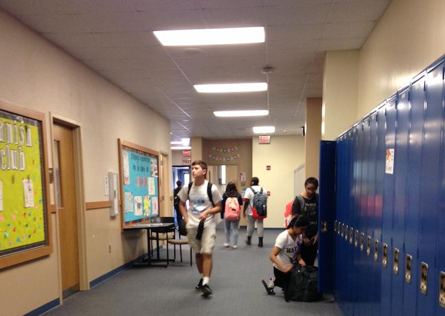 Students stop at their lockers and walk with their backpacks in the B hallway. Photo by Hallie Gallinat