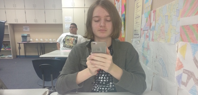 Jacob Kramer is using his phone instead of doing homework in geometry class. Photo By Seana Jordan.