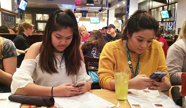 Junior Hannah Nguyen and senior Liza Fortozo check social media during dinner at Rock Bottom on Saturday, Nov. 12. The convention attendees went to multiple sessions on the convention, followed by a sponsored student dance. Photo by Madi Calvert.
