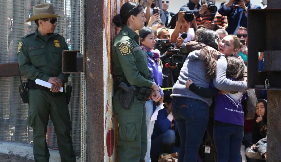 Isela Michel Zavala, left, and daughter Briana Montes embrace Yudridia Guadalupe Zavala as they meet in the Door of Hope at Borderfield State Park in San Diego on April 30, 2016.  Photo courtesy of the Tribune News Service.