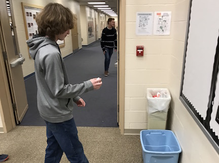 Sophomore Ethan McNanny disposes of paper in the recycling bin in the Orchestra room, which the Recycling Club clears three times a week. Photo by Ethan OSullivan.