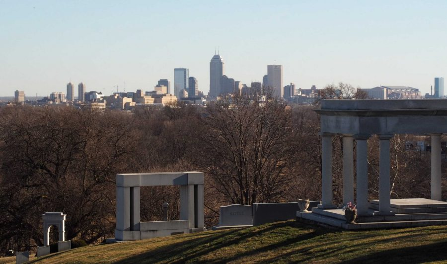 Students view the Indianapolis skyline from the James Whitcomb Riley grave at Crown Hill Cemetery. Photo by Alex Pope.
