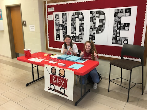 My job is to promote getting people to the dance marathon. I;m trying to get people aware of what Riley can do for the kids. sophomore Emma Gabbard said. Gabbard and Kristi Gordon promote Riley in front of a banner depicting the word Hope, created by junior Abby Rollison. Photo by Lia Benvenutti.