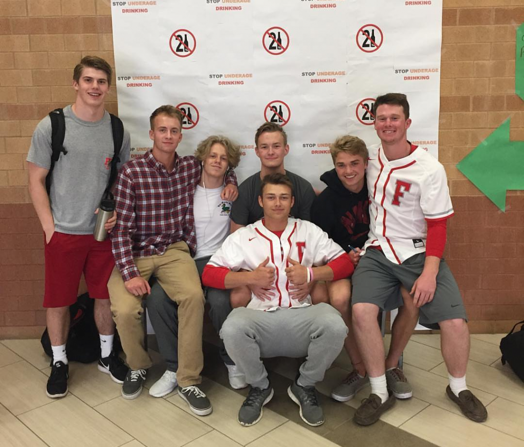 Senior Palmer Rauschenbach poses with his friends in front of the Underage Drinking Awareness poster in the cafeteria. Photo used with permission of Palmer Rauschenbach.