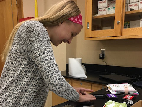 Freshman Sydney Suter laughs as she decorates her planner with stickers at Tiger Town Planners. Photo used with permission of Abigail Clone.