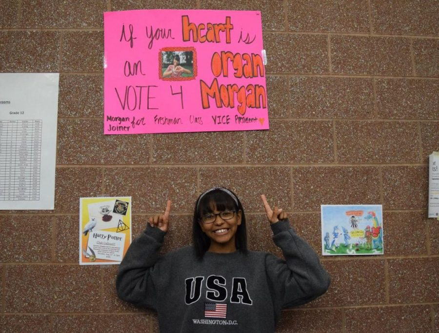Freshman+Morgan+Joiner+promotes+one+of+her+campaign+posters%2C+which+hangs+on+the+wall+near+the+bus+entrance.+Photo+taken+by+Carson+Lilley.