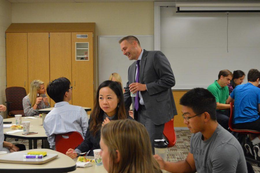 Principal Jason Urban chats with senior National Merit semi-finalist Brian Keng during the semi-finalist breakfast on Sept. 7. Photo by Mo Wood.