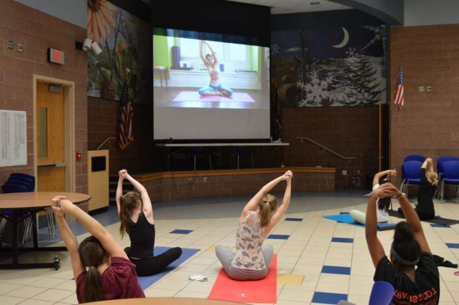 Club members follow a video by actress Adriene Mishler on August 31.  Photo by Sydney Greenwood.