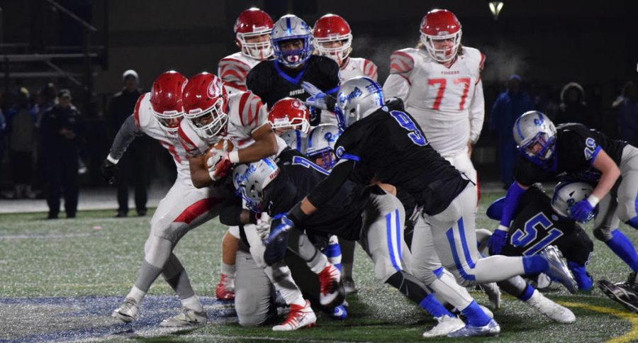 Junior running back HL Lewis pushes the ball forward on Oct. 27 as HSE defense attempts to tackle him. Tigers won 9-6. Photo by Hannah Nguyen.
