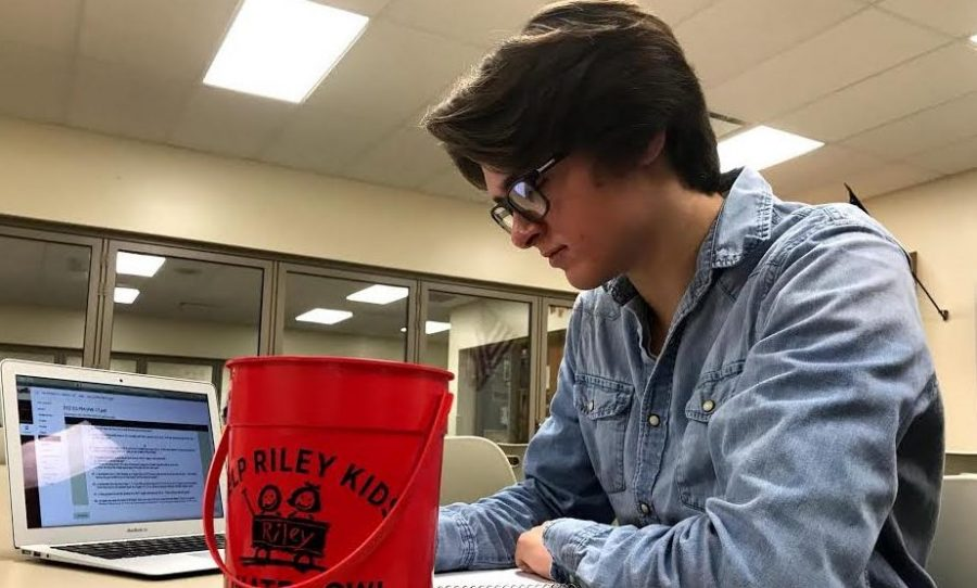 Junior Ross Delong puts his Riley Kids bucket on his desk on Nov. 1 to inform people that he is a campaign manager, raising donations for senior Brayton Wilds.