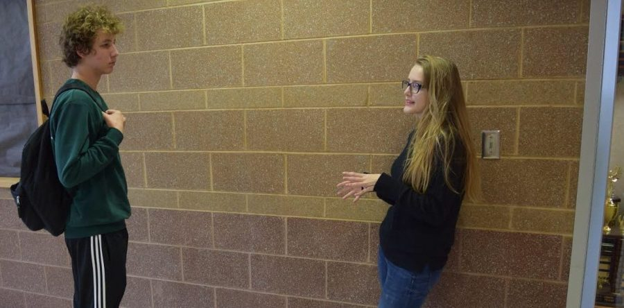 Junior Taylor Boldevitch, one of the first members of the club, talks to senior Jacob Sanderson in the hall about the Teen Dating and Domestic Violence club on Nov. 30.