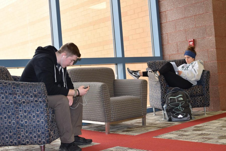 In today's society, shown by juniors Kara Natzel and Seth Daniels, young adults have several opportunities to avoid face to face interaction. Photo by Margaret Lewellen on Jan. 24.