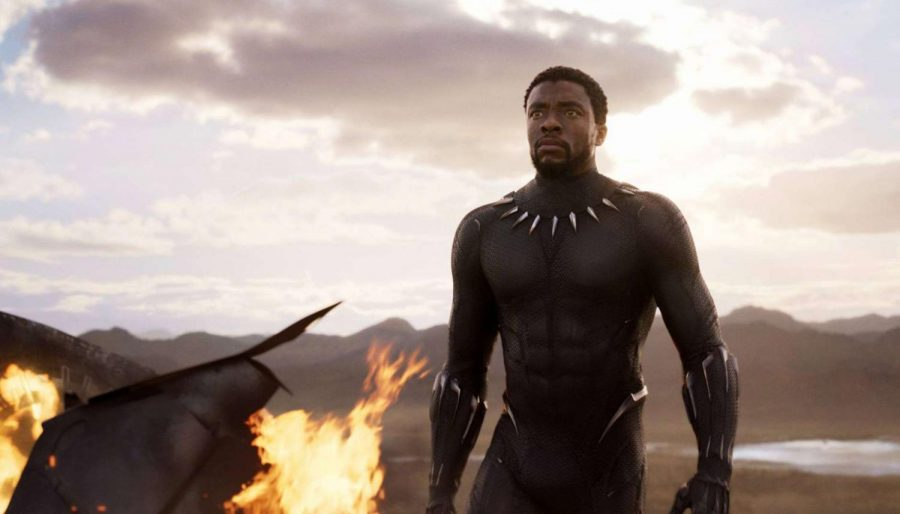 Chadwick Boseman as the Black Panther stands tall by a flaming plane as his enemies approach him. Photo used with permission of Tribune News Service.