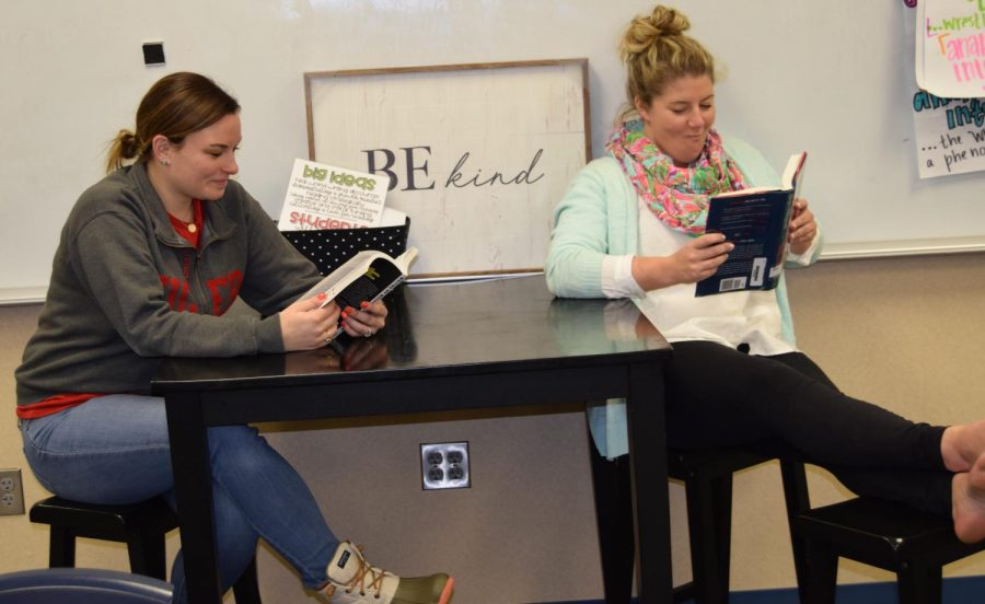 English teacher Bridgit Goss (right) reads Still Me by Jojo Moyes, with her teammate English teacher Haley Care (left) for the March Reading Madness competition. Photo by Lance Marshall on March 29.