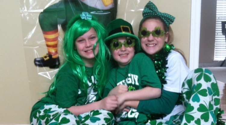 Dressed up in Saint Patricks day clothing, sophomore Mac McGuire poses for a photo with her siblings Kevin and Mary McGuire on Saint Patricks day 2014. Photo used with permission by Mac McGuire.
