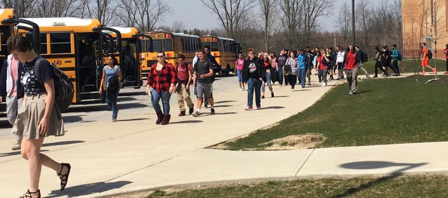 Students walk to the buses in the 70 degree weather on Thursday April 12. Photo by Hallie Gallinat.