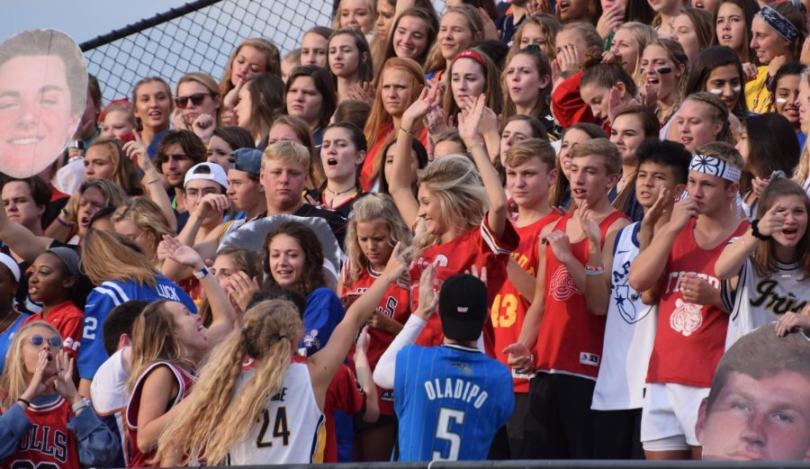 Seniors Kate Michael, Lauren Nix, Max Keithley, and the rest of the spirit team reach out to the crowd in the heat of the opening football game on August 25.