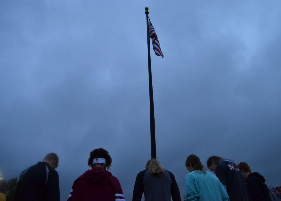 Under the waving flag, students talk about problems in the country, and pray for a solution to those problems on Sept. 26.