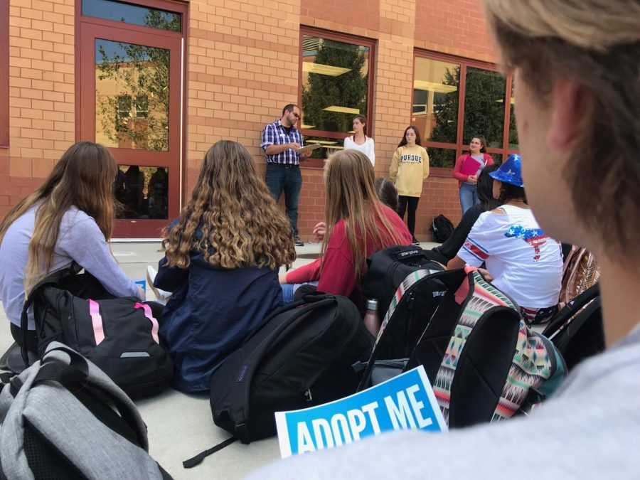 Students sit in the CCA courtyard on Sept. 13 as a Hamilton County Humane Society representative explains an event called WoofStock, which helps dogs in need.