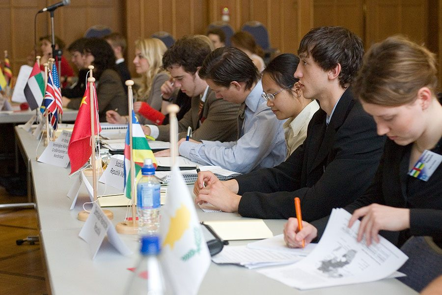 Model United Nations members from a school in Germany attend a meeting. Delegates in the committee either use nameplates or small flags to represent which country they speak for in the committee chamber.