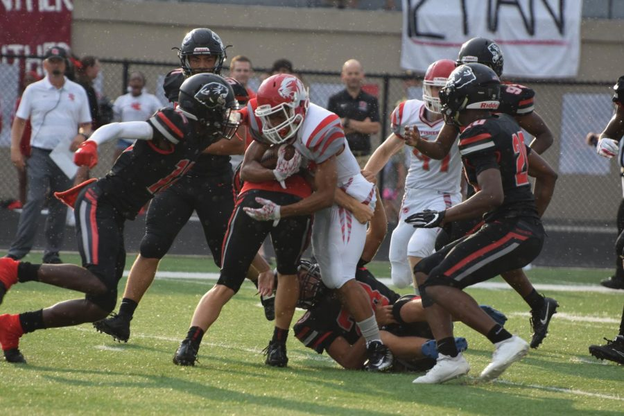 North Central players try to tackle FHS wide receiver as he heads towards the end zone. North Central won the game 31-7 on Aug. 17.