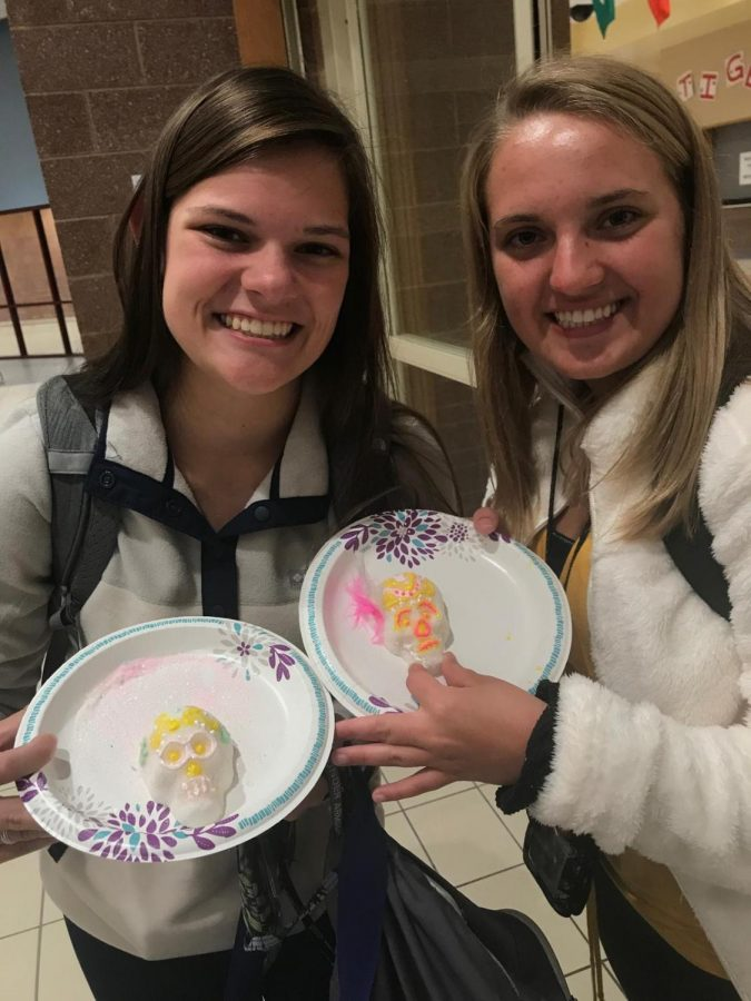 Junior Alexis Castellani and junior Candace Smallwood show off their skull candies that they decorated for the Mexican holiday Día de Muertos at the cafeteria for Spanish club during October.