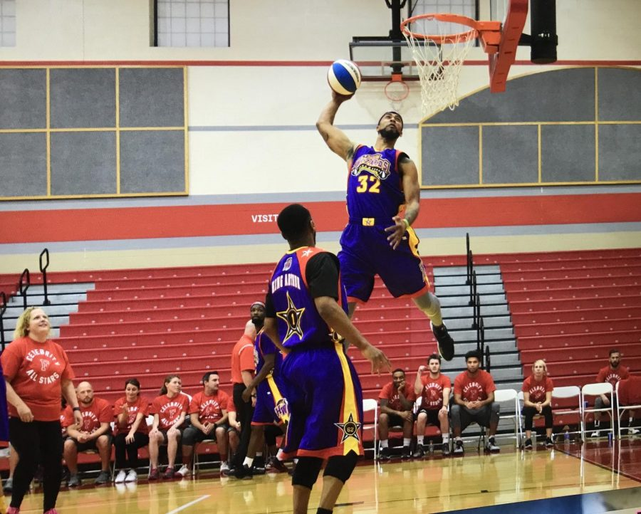 The Harlem Wizard nicknamed Space Jam goes for a dunk while King Arthur backs him up on the court during the fundraising game of 2017.