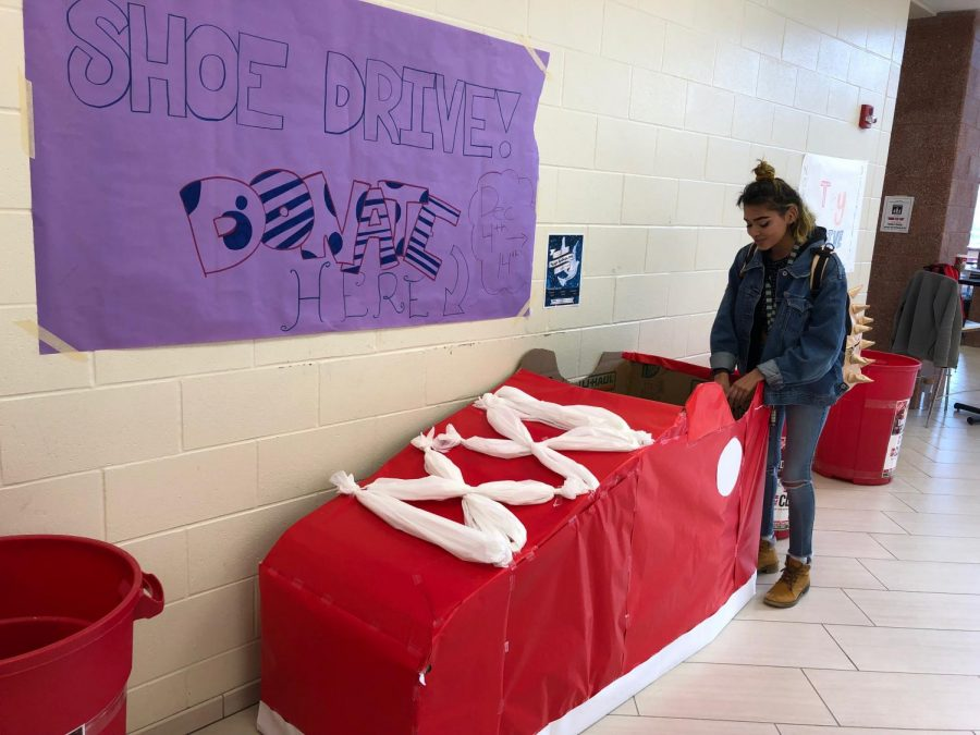 """Senior Julia Garrison donates a pair of shoes at the CCA entrance in a """"shoe box"""" made by students in Students in Action."""