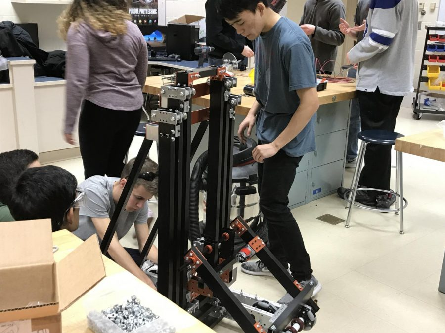 Tables around the competition robot are covered with parts as freshman Truman Mohr and junior Yuya Sawamoto work on their bot on Feb. 13.