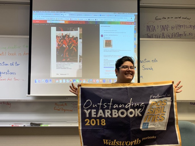 Junior James Fortozo accepts a banner commemorating his outstanding Yearbook page.