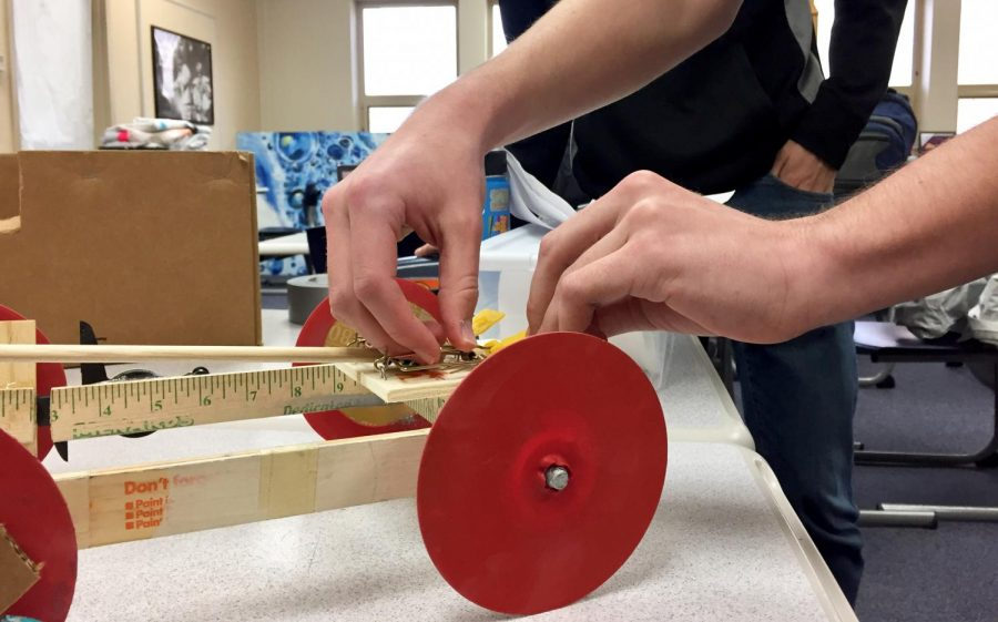 """Junior Collin Tully prepares the """"Mousetrap Vehicle"""" for a test run on Feb. 26 in room B214."""