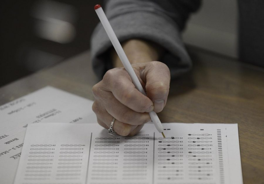 A  test taker  bubbles in her answer sheet, which has become antiquated at the rise of digital state standardized testing.
