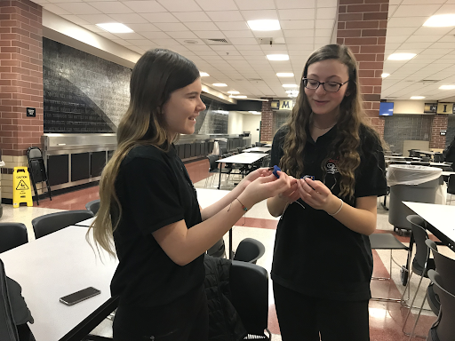 Freshmen Jenna Piccininno and Brynna Rice admire each others gold medals.