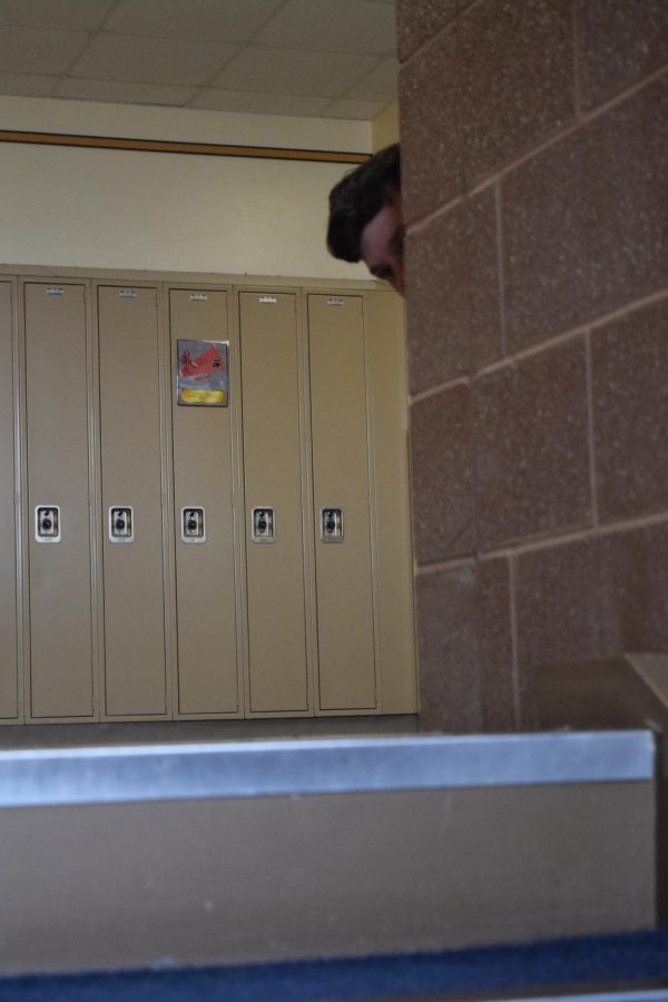Senior peaks from behind the corner. Seniors are not permitted to tag one another out on school property.