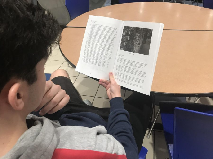 Junior Jackson Baumgartner reads a poem from last years Literary Magazine during study hall on March 14.