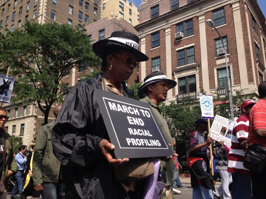 """Thousands of people march in protest of 'stop and frisk' in NYC during the Silent March to end Stop and Frisk in 2012. One of the signs reads """"March to end racial profiling."""""""