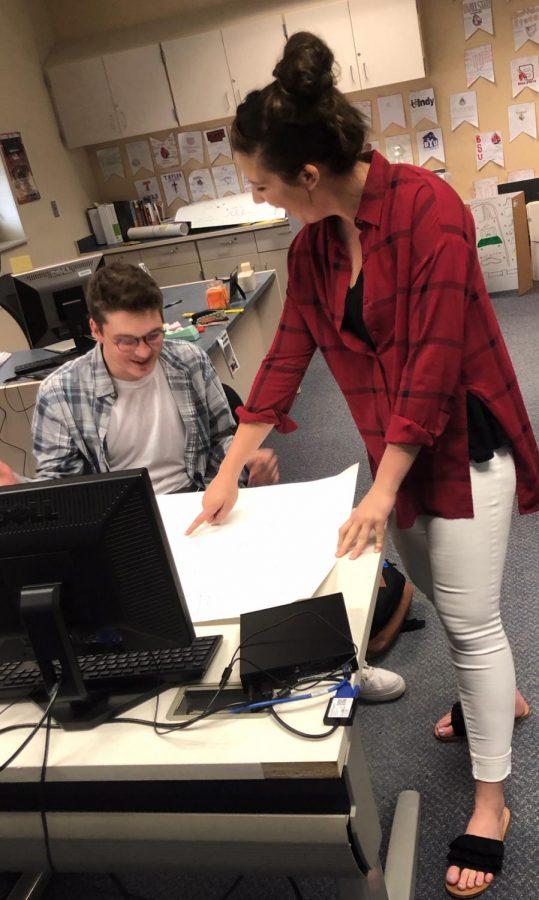 Business technology teacher Rebecca Burchette helps out senior Carson Ulmer on a roller coaster project.