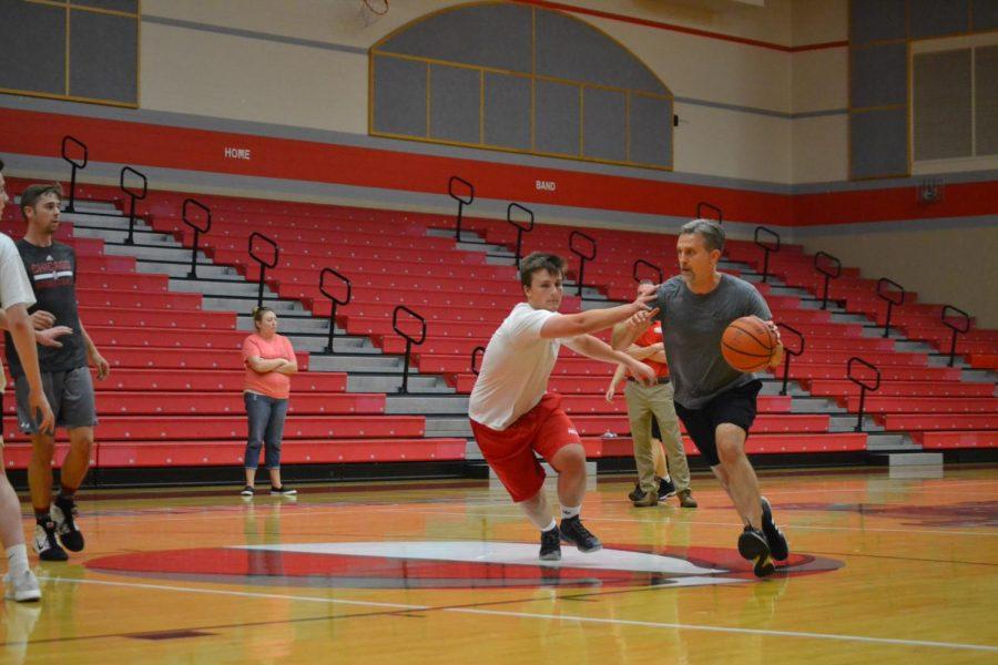 Language arts teacher Phillip Albonetti dribbles toward the basket at the three on three basketball tournament Tuesday night.