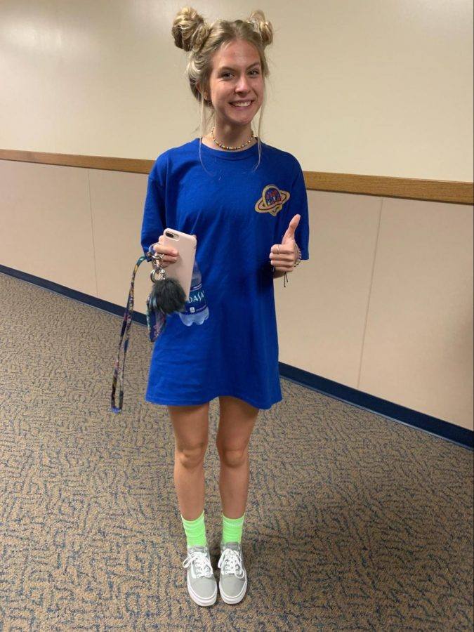 Junior Sedona Watson is wearing space buns which have been brought back since the Miley Cyrus wore them at the MTV VMA's in 2013. Space shirt: $7, pants not shown, neon green socks: $5, grey vans: $60.