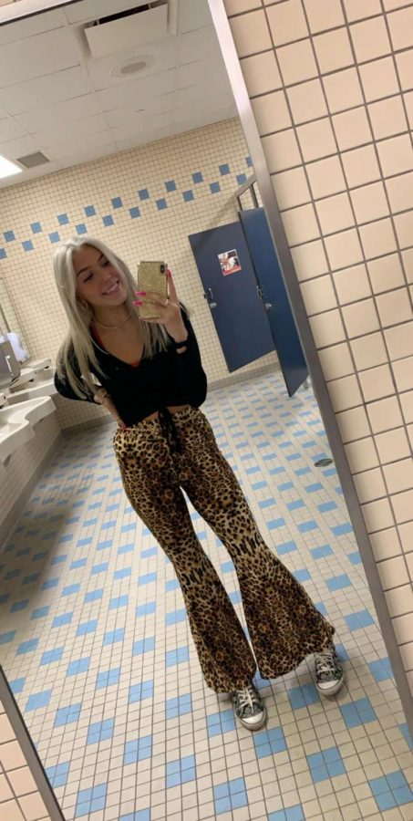Junior Jenna Wallace wears black because she is a junior. Freshmen wear white, sophomores wear grey, juniors wear black, and the seniors wear red. She is wearing a black long sleeve $, cheetah pants $15, coach shoes $45.