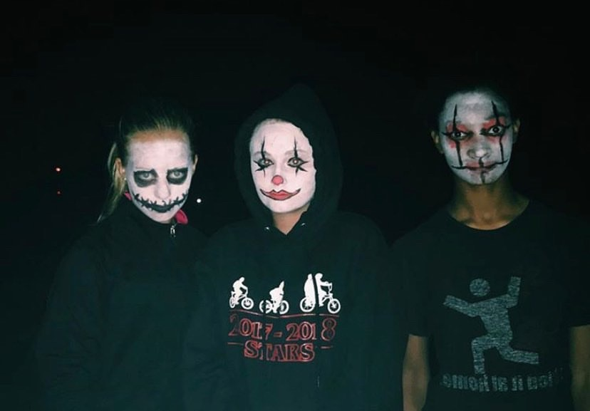 Freshmen Jillian Hooton and Maddie Marryman and Sophomore Anna Ware have their faces painted to scare people at the Haunted Trail.
