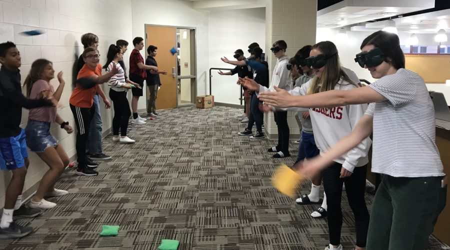 Students wearing vision altering goggles attempt to throw bean bags to their partners.