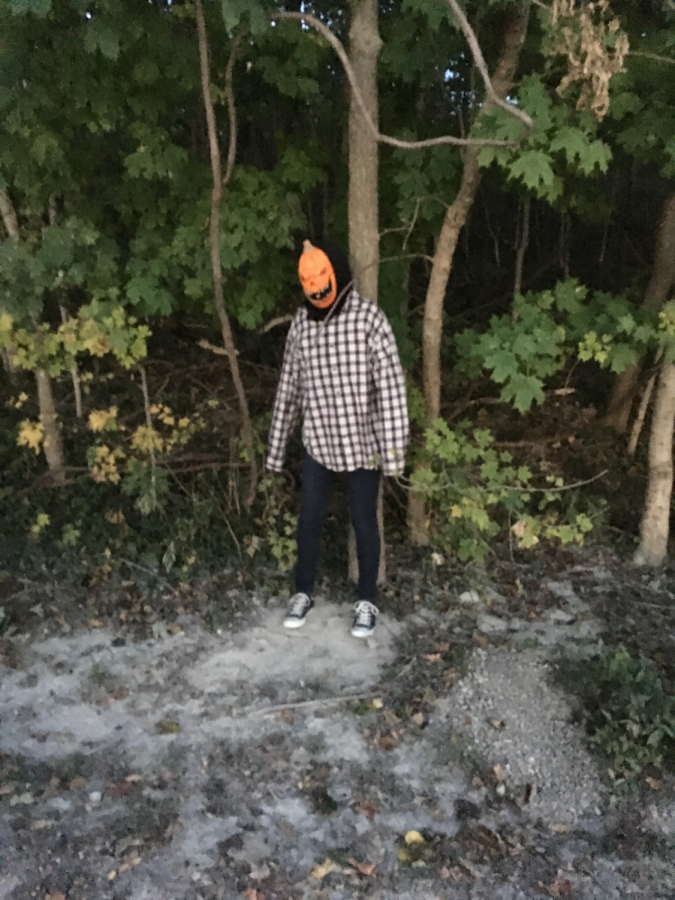 In 2015, a man in a pumpkin head mask waits in the woods of Conner Prairie to scare guests as they walk by.