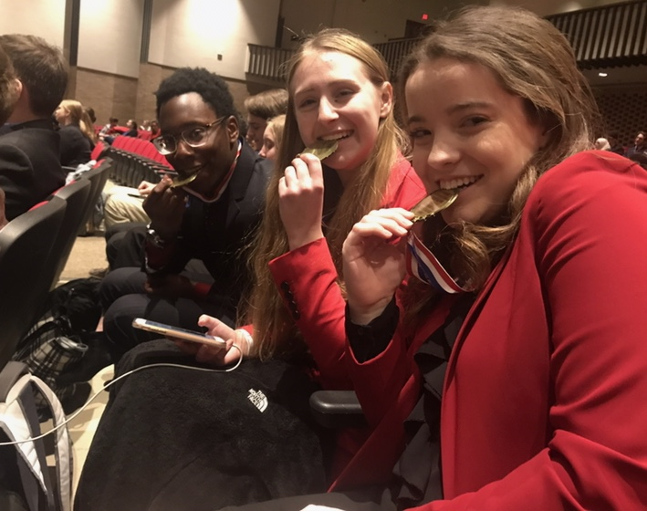 Former 2019 graduates Abidemi Aregbe, Callie Johnson and Maddie Butler bite on their first place medals for the World Schools event for debate at Southport High School on Jan. 26, 2019.