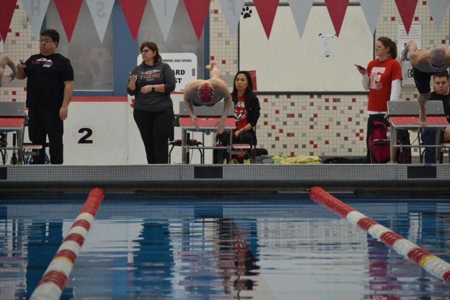 Freshman Dan Bennett dives into the water for the 100 breaststroke.